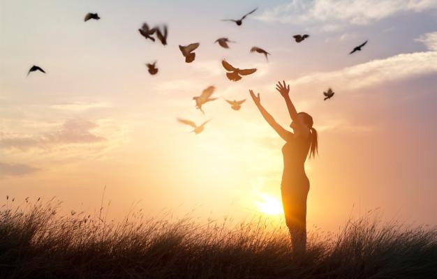 donna-che-prega-e-libera-gli-uccelli-alla-natura-su-sfondo-tramonto_34200-89